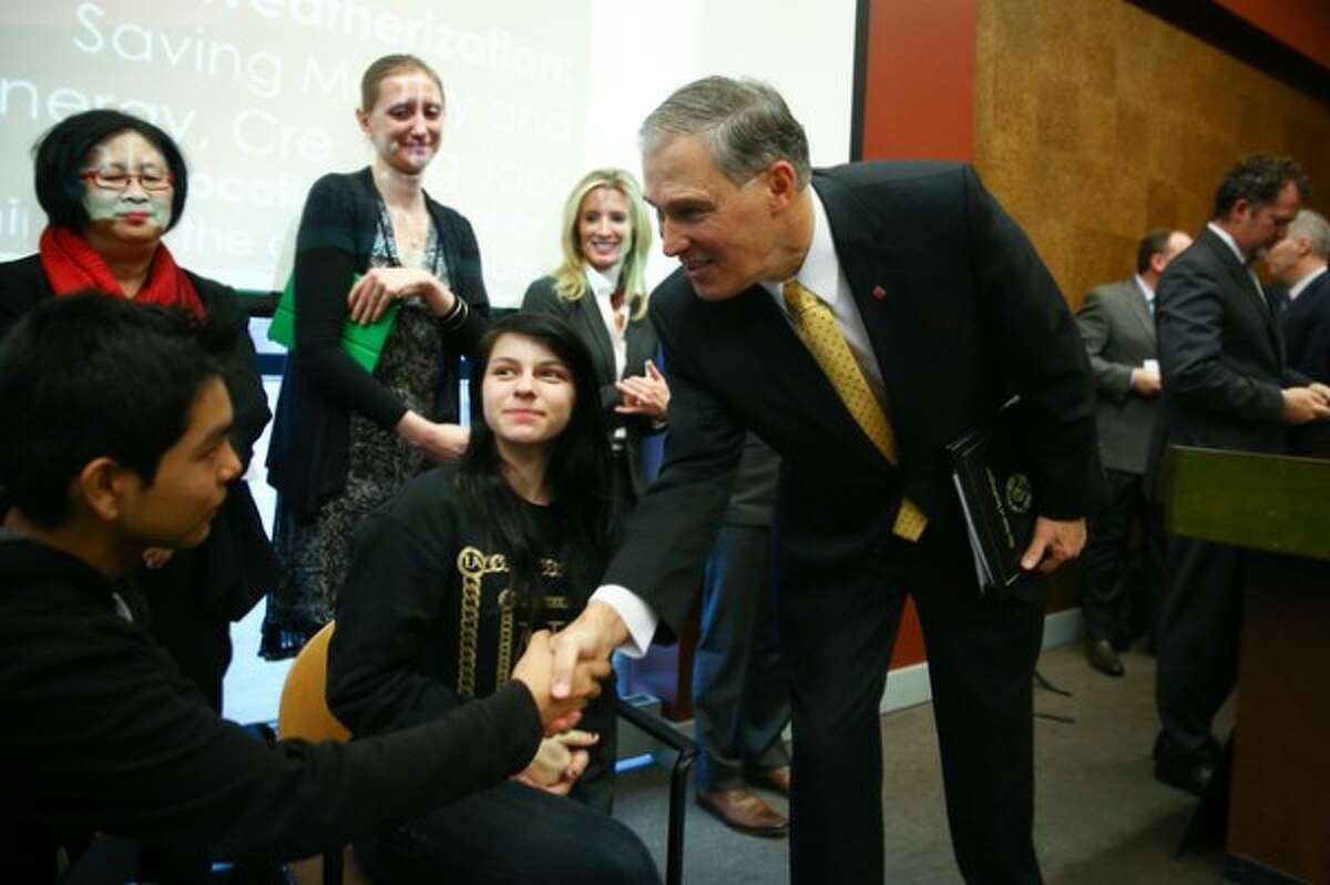 Washington Governor Jay Inslee greets Aldebaran Hernandez, 14, and Jazmyne Carlin, 13, who worked on a study about asthma in the South Park neighborhood of Seattle as Inslee formally introduced the Carbon Pollution Accountability Act.