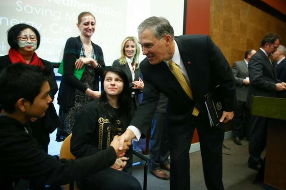 Washington Governor Jay Inslee greets Aldebaran Hernandez, 14, and Jazmyne Carlin, 13, who worked on a study about asthma in the South Park neighborhood as Inslee formally introduces the Carbon Pollution Accountability Act. It would be a tax on industries that release the most pollution into the air. (Joshua Trujillo, seattlepi.com)