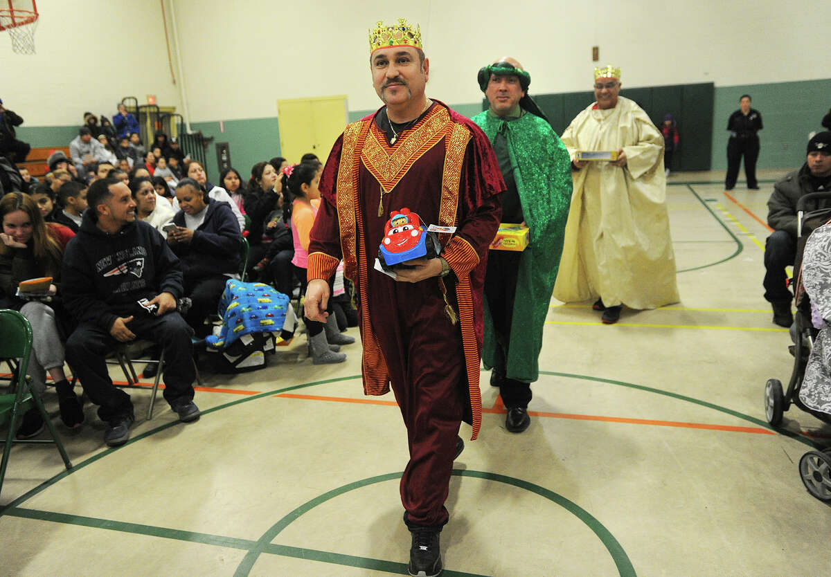 The Three Kings, played by Bridgeport Police Hispanic Society members from left; Juan Santiago, Joseph Hernandez, and Manny Cotto, process into the gymnasium for the annual Three Kings Day celebration at Luis Munoz Marin School in Bridgeport, Conn. on Tuesday, January 6, 2015.