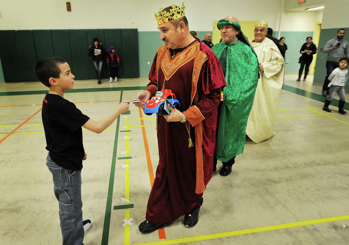 Dustin Bonilla, 8, of Bridgeport, hands a letter to Juan Santiago, of Bridgeport, during the annual Three Kings Day celebration at Luis Munoz Marin School in Bridgeport, Conn. on Tuesday, January 6, 2015. The kings were played by Bridgeport Police Hispanic Society members from left; Santiago, Joseph Hernandez, and Manny Cotto.