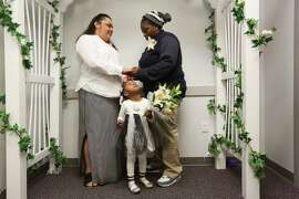 Virginia (left) and Marrekia Jeffries of Foley, Ala., exchange vows at the county courthouse in Pensacola, Fla., joined by niece Tia'miya Robinson.