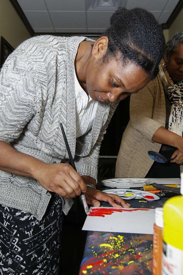 Vision board participant Chere uses paint to start her personal board at a demonstration and board building event held at Center Stage Gallery in Sugar Land on December 28, 2014. Photo: Diana L. Porter, Freelance / © Diana L. Porter