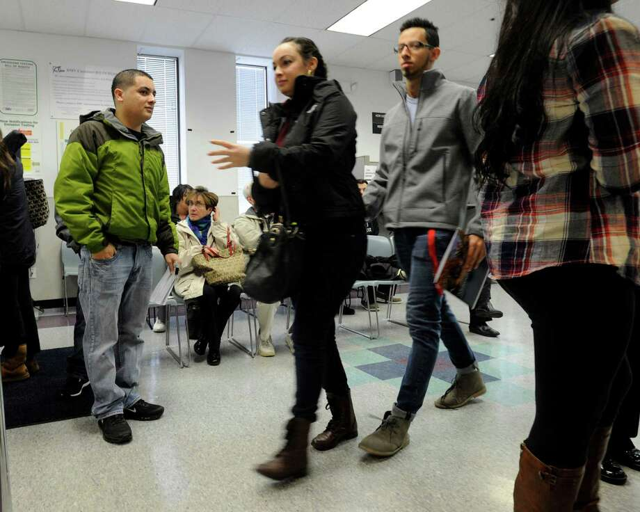Juan Lopez Luna, left, a native of Honduras who has been in the U.S. for eight years, waits his turn in line during his application process for a driver's license at the Department of Motor Vehicles in Danbury, Conn., Tuesday, January 6, 2015. He is not a U.S. citizen. Photo: Carol Kaliff / The News-Times