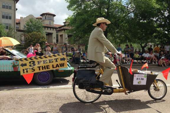 A bicyclist rides in the 2014 Houston Art Car Parade to raise awareness of the city's safe passing law, which requires drivers to give cyclists and pedestrians three feet of space, on May 10, 2014 in Houston.