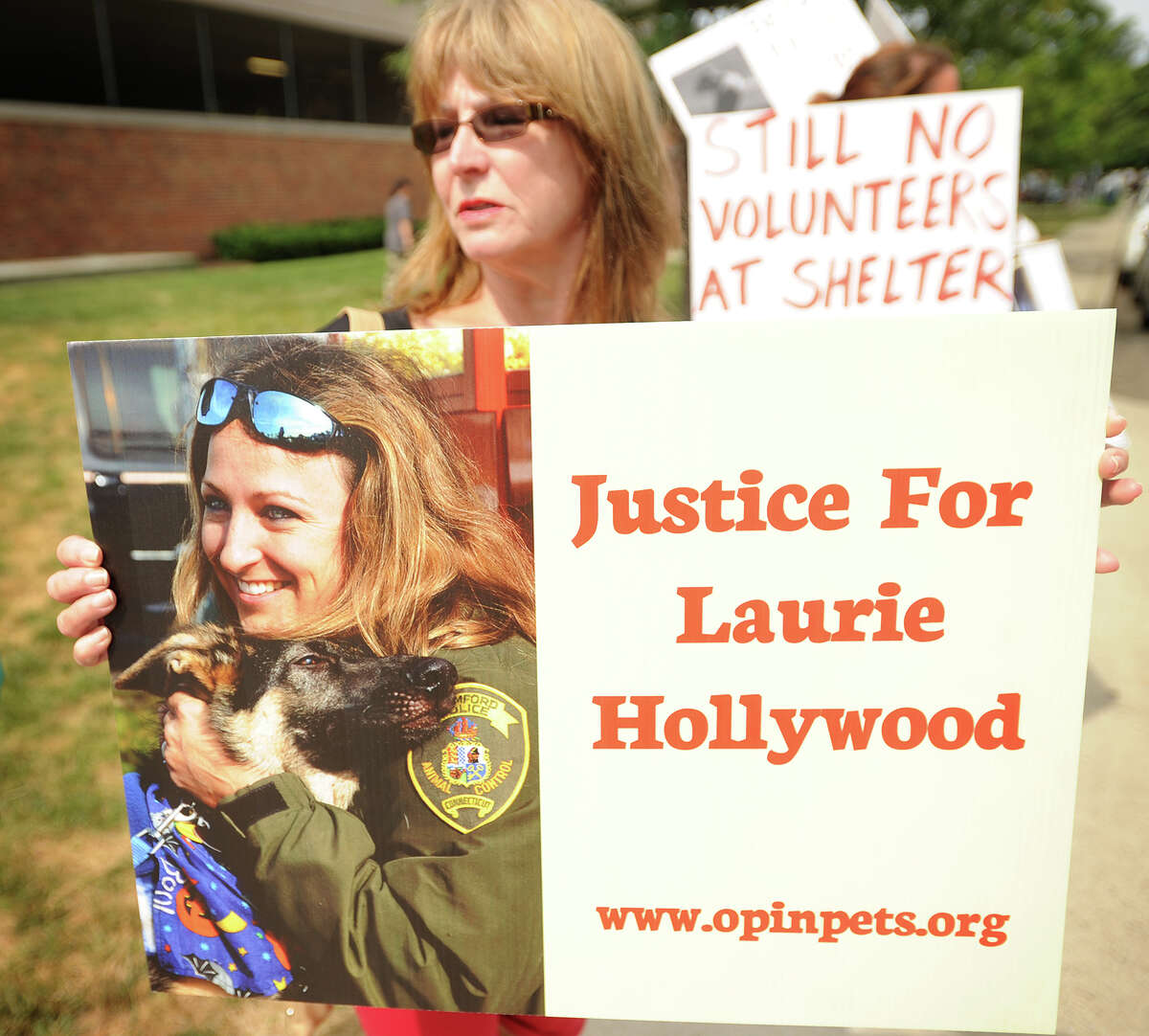 Leslie Bruzik, of Stamford, holds a sign in support of former Stamford Animal Shelter Director Laurie Hollywood outside Superior Court in Stamford, Conn. on Thursday, July 10, 2014.