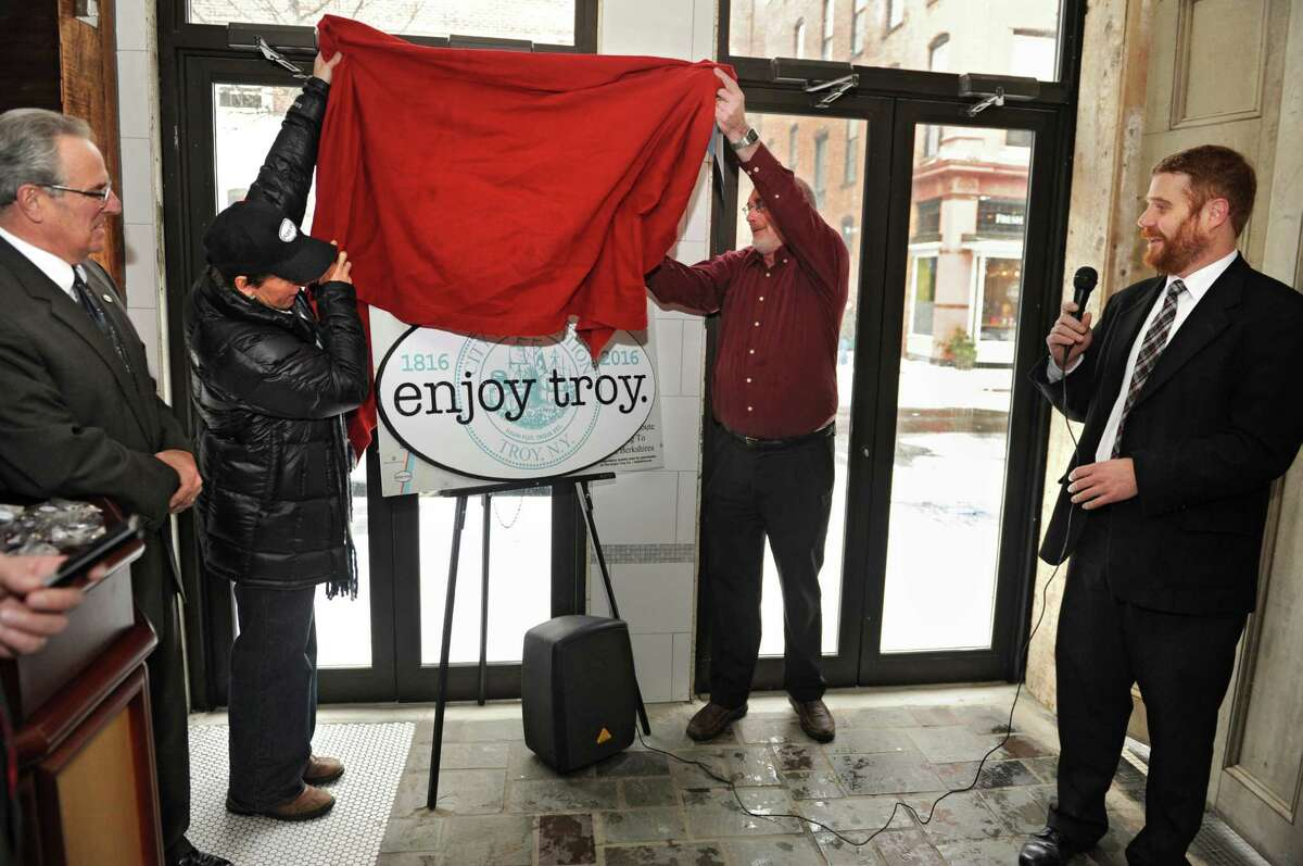 Troy Mayor Lou Rosamilia watches at left as Linda Passaretti and Tom Reynolds of The Enjoy Troy Co. unveil the enjoy troy emblem at Peck's Arcade on Tuesday, Jan. 6, 2015 in Troy, N.Y. Troy writer Duncan Crary stands at right. (Lori Van Buren / Times Union)