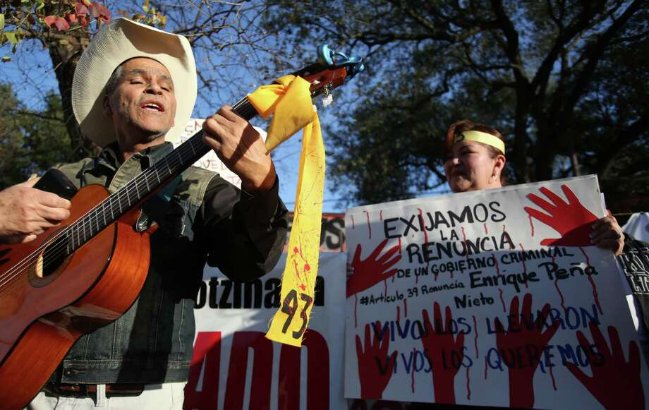 """A bloody ribbon with the #43 hangs from Javier Ambriz guitar as he joins activists in a rally outside the Mexican Consulate for the 43 missing students from Ayotzinapa and to """"unwelcome"""" President Peña Nieto's visit with President Obama today on Tuesday, Jan. 6, 2015, in Houston. Photo: Mayra Beltran, Houston Chronicle / © 2015 Houston Chronicle"""