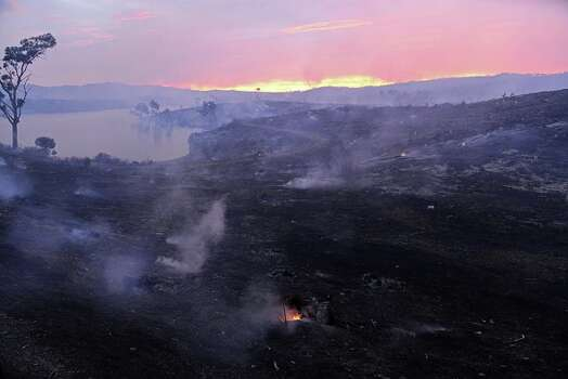 In a picture taken on Jan. 3, 2015, embers glow against the smoke-filled sunset near Gumeracha in the Adelaide Hills. More than 30 homes are feared destroyed as firefighters battle the worst bushfire in South Australia for three decades, with officials warning on January 4 of a threat to lives even as weather conditions improve. Photo: BRENTON EDWARDS, Brenton Edwards/AFP/Getty Images / AFP