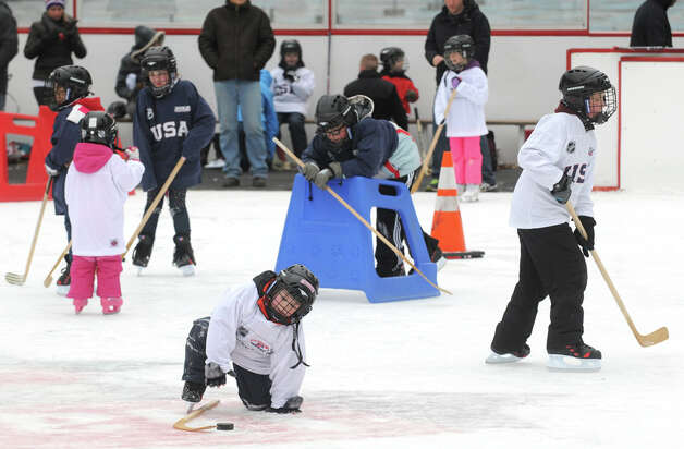 Children and instructors take to the ice during a event designed to provide kids ages 4 to 9 a free experience to try youth hockey at the Empire State Plaza ice rink on Saturday Jan. 3, 2015 in Albany, N.Y. (Michael P. Farrell/Times Union) Photo: Michael P. Farrell, Albany Times Union / 00029990A