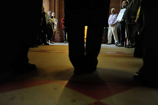 People take part in a prayer circle during a rally at the Capitol on Monday, Jan. 5, 2015, in Albany, N.Y.  The rally was held to call on legislators to move forward with a policy agenda that prioritizes good jobs with living wages.  (Paul Buckowski / Times Union) Photo: Paul Buckowski, Albany Times Union / 00030075A