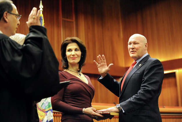 Assemblyman Peter Lawrence of the 134th District, right, takes the oath of office from Hon. Kevin J. Engel of the Town of East Greenbush, left, on Tuesday, Jan. 6, 2015, at the Legislative Office Building in Albany, N.Y. Joining him is his wife Tanya Lawrence. (Cindy Schultz / Times Union) Photo: Cindy Schultz, Albany Times Union / 00030090A