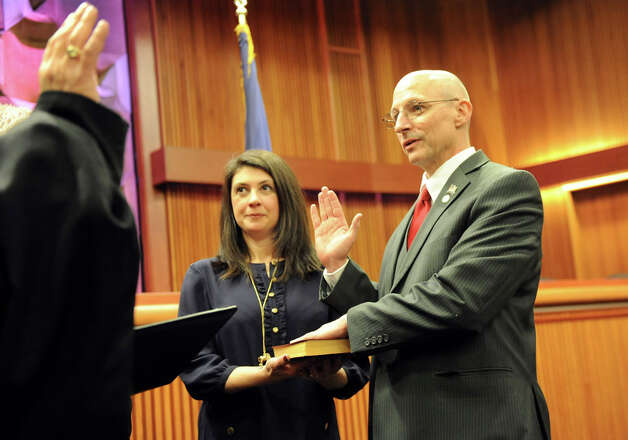Assemblyman Dean Murray of the 3rd District, right, takes the oath of office from Hon. Kevin J. Engel of the Town of East Greenbush, left, on Tuesday, Jan. 6, 2015, at the Legislative Office Building in Albany, N.Y. Joining him is his wife Amy Illardo-Murray. (Cindy Schultz / Times Union) Photo: Cindy Schultz, Albany Times Union / 00030090A