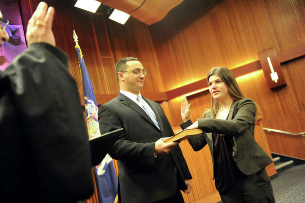 Assemblywoman Angela Wozniak of the 134th District, right, takes the oath of office from Hon. Kevin J. Engel of the Town of East Greenbush, left, on Tuesday, Jan. 6, 2015, at the Legislative Office Building in Albany, N.Y. Joining her is her husband Phil Drenning. (Cindy Schultz / Times Union) Photo: Cindy Schultz, Albany Times Union / 00030090A