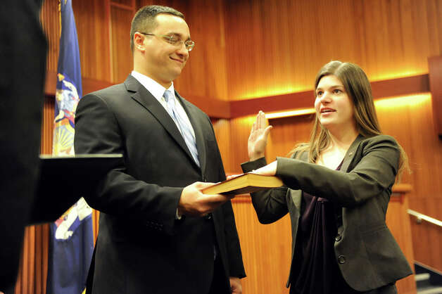 Assemblywoman Angela Wozniak of the 134th District, right, takes the oath of office as her husband Phil Drenning holds the Bible on Tuesday, Jan. 6, 2015, at the Legislative Office Building in Albany, N.Y. (Cindy Schultz / Times Union) Photo: Cindy Schultz, Albany Times Union / 00030090A