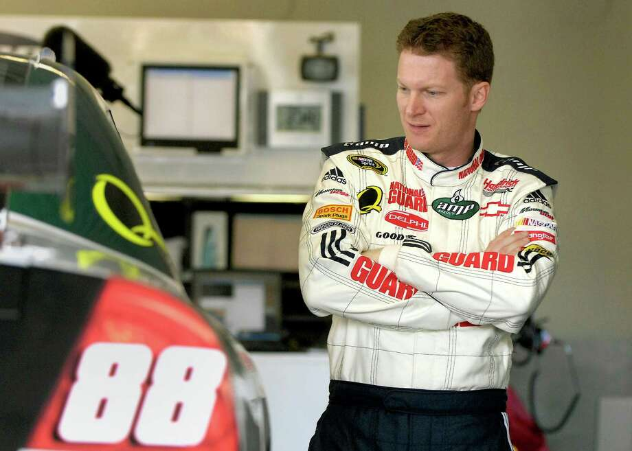 Dale Earnhardt Jr. glances at his National Guard/Mountain Dew/AMP Energy race car in 2008. Some have jokingly suggested that members of Congress wear suits like NASCAR drivers so everyone can see who their sponsors are. Photo: Jeff Siner, MBR / Charlotte Observer