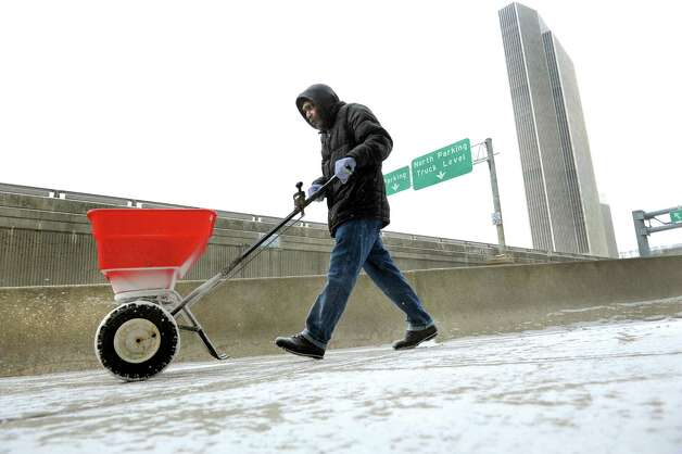 Snow crew member Sean DuPree spread salt on the walkway on Tuesday, Jan. 6, 2015, at Times Union Center in Albany, N.Y. (Cindy Schultz / Times Union) Photo: Cindy Schultz / 00030092A