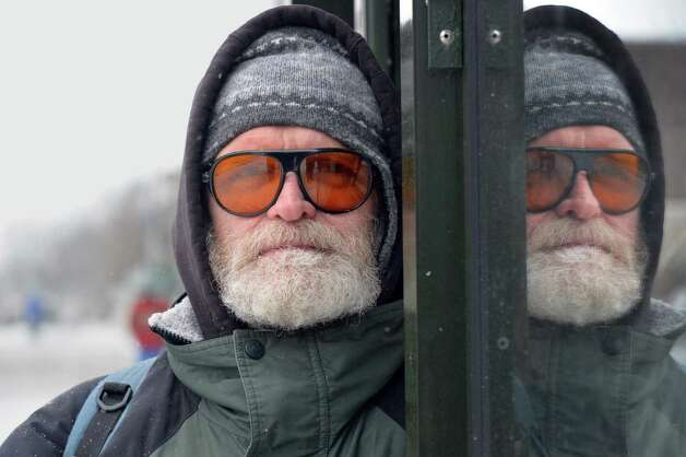 Zoe Morgan Sydney of Albany shields himself from a cold wind as he waits for a bus on Washington Ave. Tuesday Jan. 6, 2015, in Albany, NY.   (John Carl D'Annibale / Times Union) Photo: John Carl D'Annibale