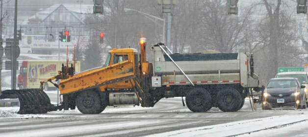 A state department of transportation snowplow crosses Everett Road Tuesday, Jan. 6, 2015, in Albany, N.Y.   (John Carl D'Annibale / Times Union) Photo: John Carl D'Annibale