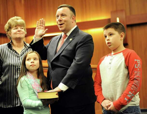 Assemblyman Karl Brabenec of the 98th District, center, takes the oath of office on Tuesday, Jan. 6, 2015, at the Legislative Office Building in Albany, N.Y. Joining him, from left, are his mother Emilie Brabenec, his daughter Kimberlee, 9, and his son Karl, 10. (Cindy Schultz / Times Union) Photo: Cindy Schultz / 00030090A