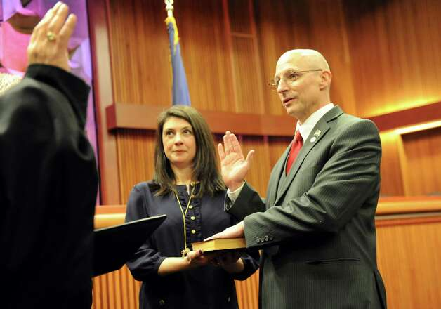 Assemblyman Dean Murray of the 3rd District, right, takes the oath of office from Hon. Kevin J. Engel of the Town of East Greenbush, left, on Tuesday, Jan. 6, 2015, at the Legislative Office Building in Albany, N.Y. Joining him is his wife Amy Illardo-Murray. (Cindy Schultz / Times Union) Photo: Cindy Schultz / 00030090A