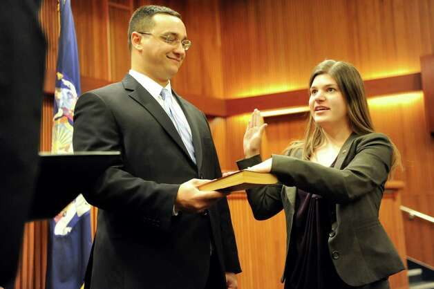 Assemblywoman Angela Wozniak of the 134th District, right, takes the oath of office as her husband Phil Drenning holds the Bible on Tuesday, Jan. 6, 2015, at the Legislative Office Building in Albany, N.Y. (Cindy Schultz / Times Union) Photo: Cindy Schultz / 00030090A