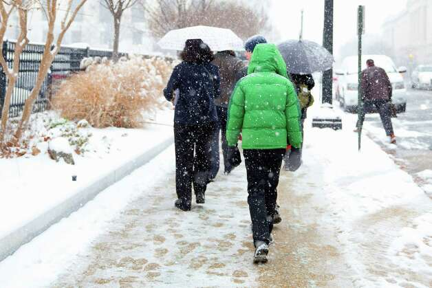 People walk in the snow toward the Capitol in Washington, Tuesday, Jan. 6, 2015, on the start of the 114th Congress in Washington. (AP Photo/Jacquelyn Martin) ORG XMIT: DCJM104 Photo: Jacquelyn Martin / AP
