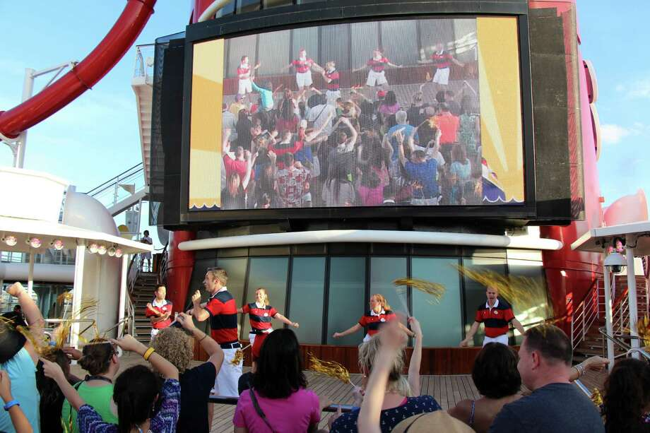 A large television screen projects on-deck entertainment aboard the cruside ship, Disney Magic. Photo: Contributed Photo / Westport News
