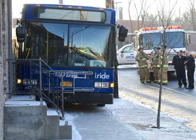A Capital District Transportation Authority bus sits wedged between a power pole and a porch on Congress Street in Troy on Wednesday, Jan. 7, 2015. Police said at least five people suffered minor injuries in the crash that occurred shortly before 8 a.m. (Skip Dickstein / Time Union)