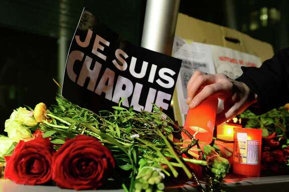 """A man lights a candle next to a poster reading """"Je suis Charlie"""" (I am Charlie) in front of the French embassy on January 7, 2015 in Berlin to express solidarity with employees of the French satirical weekly Charlie Hebdo that has been target of  an attack by unknown gunmen. German Chancellor Angela Merkel condemned the """"despicable"""" attack on Charlie Hebdo that left at least 12 people dead in a condolence letter to President Francois Hollande.       AFP PHOTO / JOHN MACDOUGALLJOHN MACDOUGALL/AFP/Getty Images"""