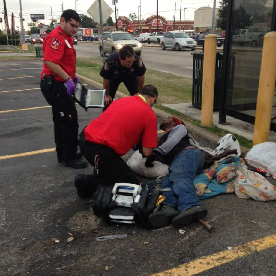 EMS workers talk with Michael Franklin, a homeless man, who was found sleeping behind a Metro bus stop. Franklin, who was unable to stand on his own, was taken to a local hospital for treatment Photo: Bryan Kirk