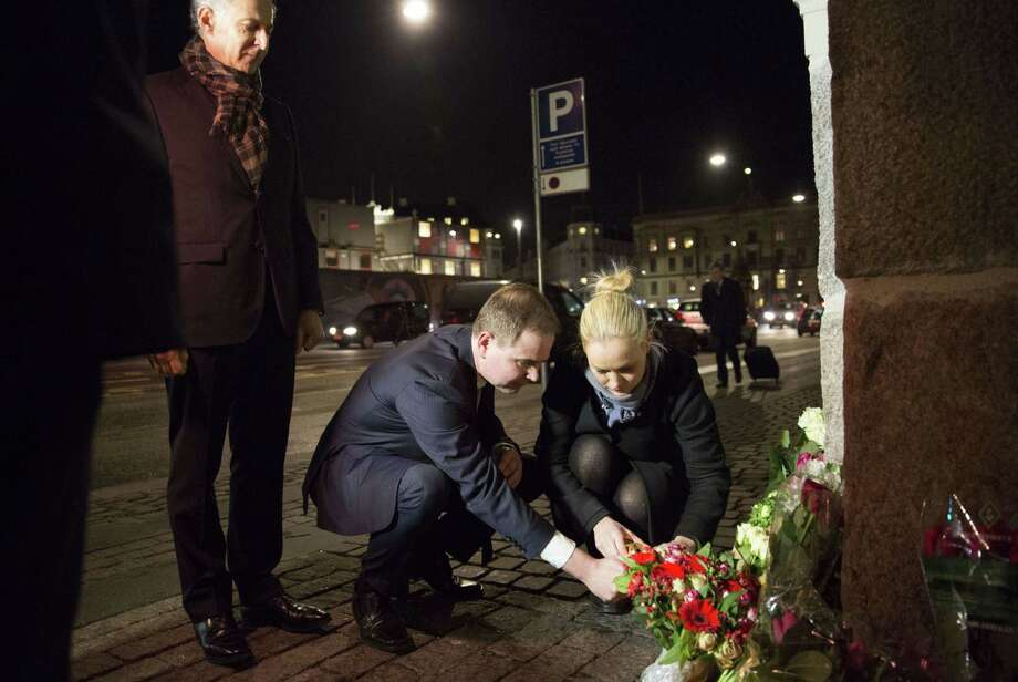 The French Ambassador to Denmark, Francois Zimeray (L), looks on as Nicolai Wammen (C), Danish Minister of Defense, lights a candle in front of the French Embassy in Copenhagen on January 7, 2015 after the attacks on the French satirical magazine Charlie Hebdo in Paris earlier today.            AFP PHOTO / SCANPIX DENMARK / ERIK REFNER +++ DENMARK OUTERIK REFNER/AFP/Getty Images Photo: ERIK REFNER / AFP/Getty Images / AFP