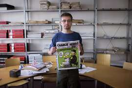 """French satirical weekly Charlie Hebdo's publisher, known only as Charb, presents to journalists, on September 19, 2012 in Paris, at the headquarters, the last issue which features on the front cover a satirical drawing titled """"Intouchables 2"""". Inside pages contain several cartoons caricaturing the Prophet Mohammed. The magazine's decision to publish the cartoons came against a background of unrest across the Islamic world over a crude US-made film that mocks Mohammed and portrays Muslims as gratuitously violent. The title refers to """"Intouchables"""", a 2012 French movie, the most seen French movie abroad, which is selected to represent France for the Oscars nominees, according to one of his directors, Eric Toledano. AFP PHOTO FRED DUFOURFRED DUFOUR/AFP/GettyImages"""