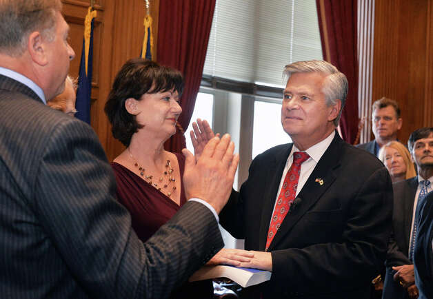 NYS Senate GOP leader Dean Skelos, right, is joined by his wife Gail, center, as he is sworn in by Nassau County Judge Thomas Adams, left, during a ceremony at the Capitol Wednesday Jan. 7, 2015, in Albany, NY.  (John Carl D'Annibale / Times Union) Photo: John Carl D'Annibale, Albany Times Union / 00030091B
