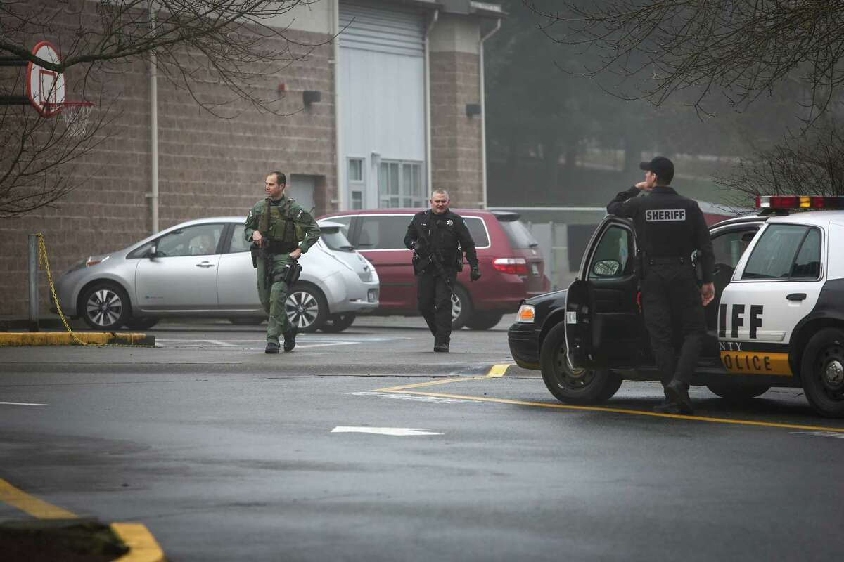 Deputies with automatic rifles search the grounds of The Evergreen School after a man with a gun was seen at nearby Meridian Park School in Shoreline on Wednesday, January 7, 2015. An employee of the school said the man threatened the school, prompting the closure of schools across the district.