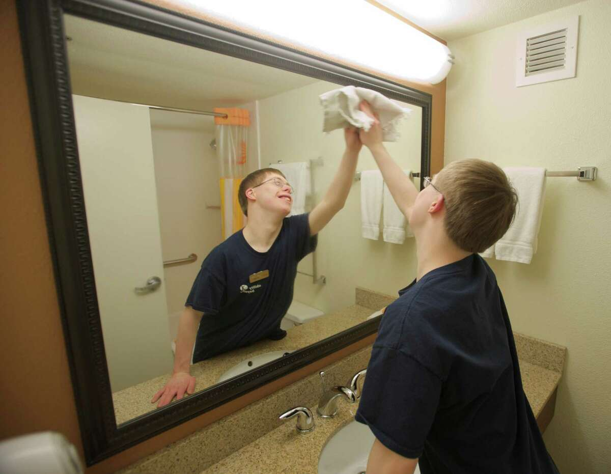 Evan Wagman, age 22, of Bethel, cleans a mirror at La Quinta Inn & Suites in Danbury this spring. Wagman is in the ATLAS program at Ability Beyond which helps prepare young adults with developmental disabilities for employment. Participants were training at the hotel.