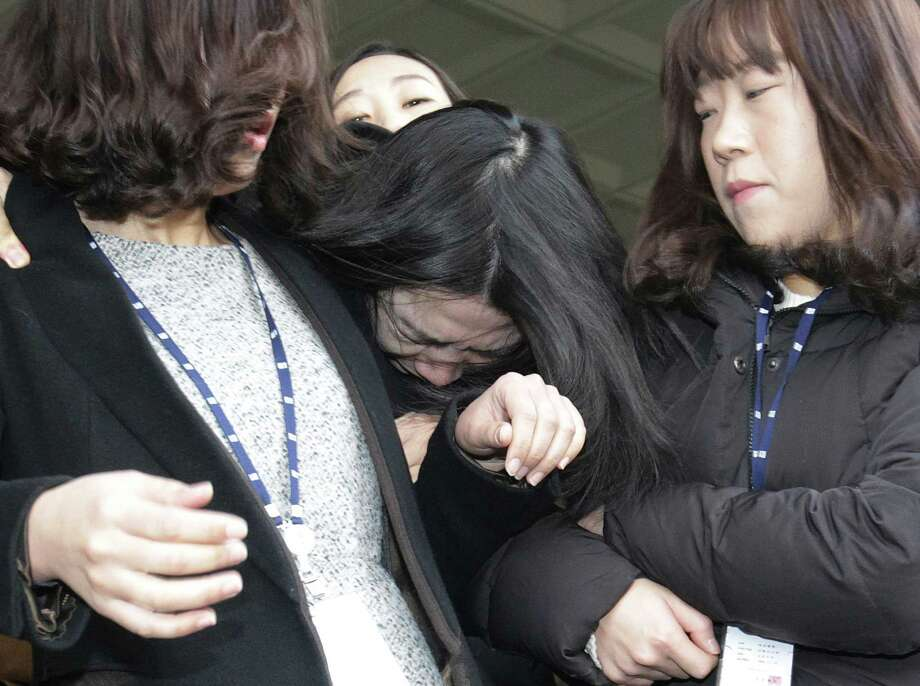 """FILE - In this Tuesday, Dec. 30, 2014 file photo, Cho Hyun-ah, center, former vice president of Korean Air Lines, is escorted by court officials as she leaves for Seoul Western District Prosecutors Office at the Seoul Western District Court Office in Seoul, South Korea. South Korean prosecutors on Wednesday charged the former Korean Air Lines executive who achieved worldwide notoriety by kicking a crew member off a flight with violating aviation security law and hindering a government investigation. Cho's actions amounted to """"threatening the safety of the flight and causing confusion in law and order,"""" prosecutor Kim Chang-hee said during a briefing that was broadcast live by local television networks. (AP Photo/Ahn Young-joon, File) Photo: Ahn Young-joon / Associated Press / AP"""