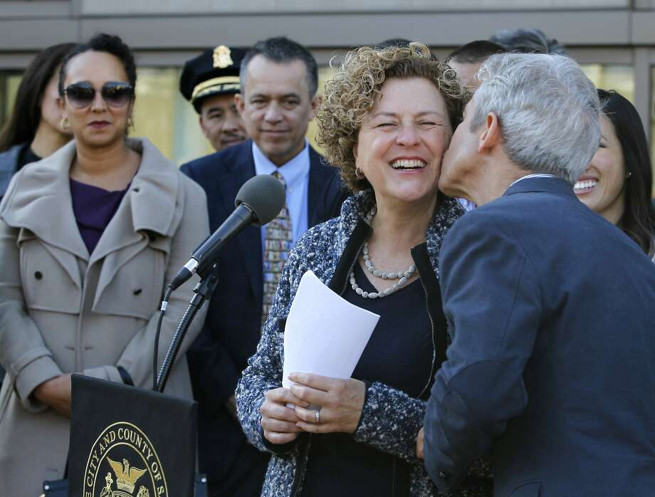 Julie Christensen gets a kiss from her husband Greg Smith after she was appointed by Mayor Ed Lee to fill the vacant District 3 seat on the Board of Supervisors in San Francisco, Calif. on Wednesday, Jan 7, 2015. Christensen takes over from David Chiu, who was elected to the state assembly in November. Photo: Paul Chinn, The Chronicle