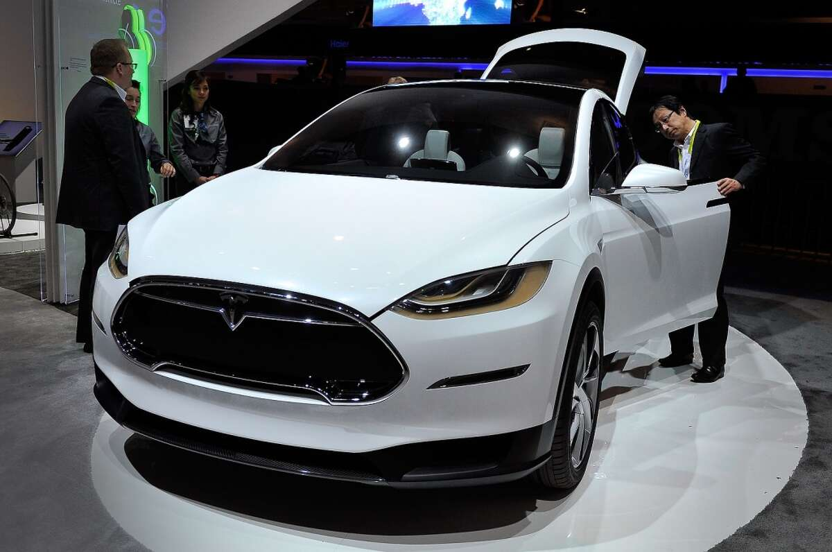 An attendee looks over the Telsa Model X, all electric vehicle, at the Panasonic booth at the 2015 International CES at the Las Vegas Convention Center on January 6, 2015 in Las Vegas, Nevada. CES, the world's largest annual consumer technology trade show, runs through January 9 and is expected to feature 3,600 exhibitors showing off their latest products and services to about 150,000 attendees.