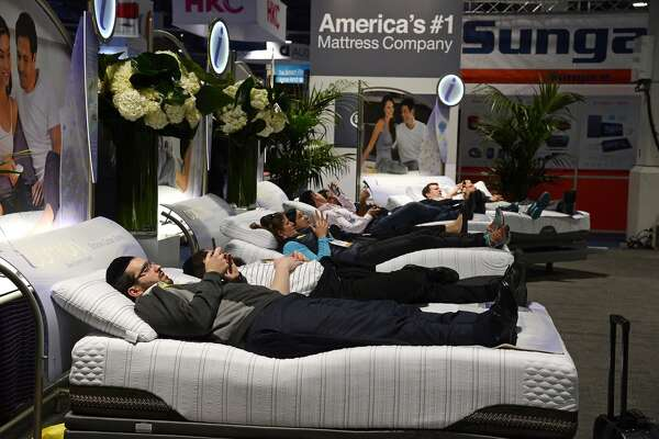 Attendees lay on Serta mattresses at the Serta stand, January 6, 2015 at the Consumer Electronics Show in Las Vegas, Nevada.