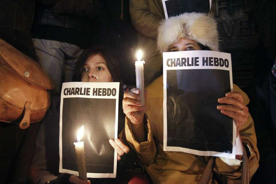PARIS, FRANCE - JANUARY 07:  Women hold candles during a gathering at the Place de la Republique (Republic square) in support of the victims after the terrorist attack earlier today on January 7, 2015 in Paris, France. Twelve people were killed including two police officers as two gunmen opened fire at the offices of the French satirical publication Charlie Hebdo.  (Photo by Thierry Chesnot/Getty Images) Photo: Thierry Chesnot, Stringer / 2015 Getty Images