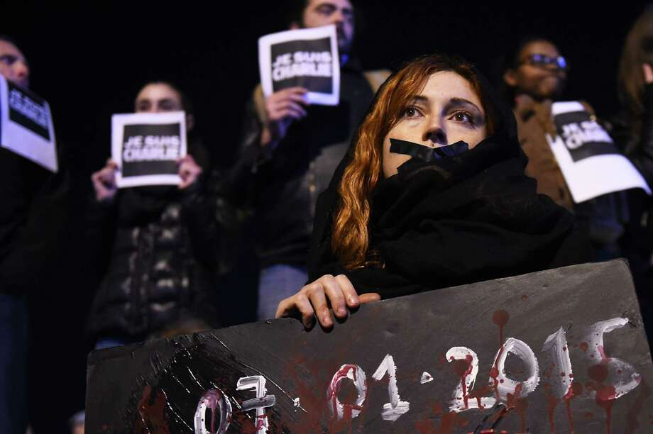 """People hold placard reading """"I am Charlie"""" during a gathering on the Old Harbor in Marseille on January 7, 2015, following an attack by unknown gunmen on the offices of the satirical weekly, Charlie Hebdo. France's Muslim leadership sharply condemned the shooting at the Paris satirical weekly that left at least 12 people dead as a """"barbaric"""" attack and an assault on press freedom and democracy. AFP PHOTO / ANNE-CHRISTINE POUJOULATANNE-CHRISTINE POUJOULAT/AFP/Getty Images Photo: ANNE-CHRISTINE POUJOULAT / AFP/Getty Images / AFP"""