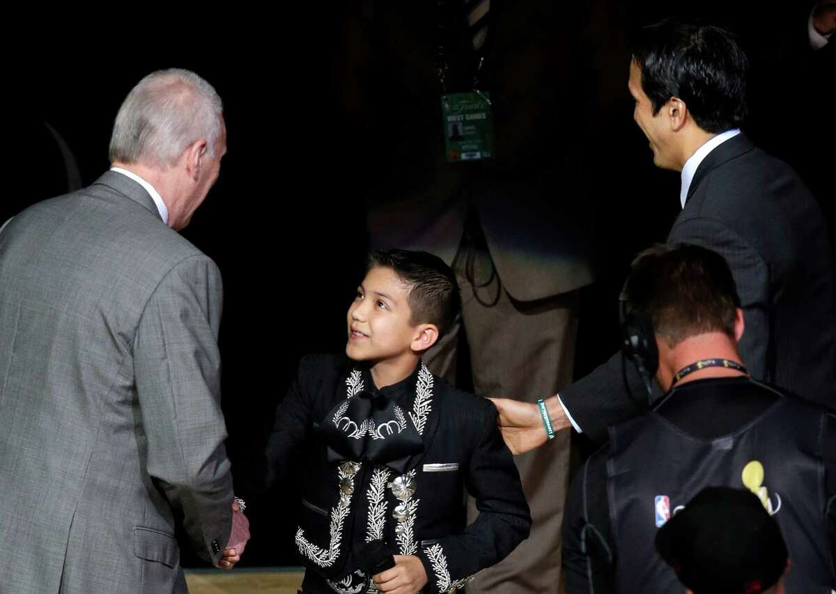Sebastien De la Cruz is greeted by San Antonio Spurs' Gregg Popovich (left) and Miami Heat's Erik Spoelstra after singing the national anthem before Game 4 of the NBA Finals basketball series, on June 13, 2013, in San Antonio.
