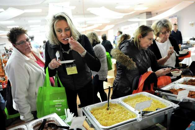 Renee Hanks, food director with South Colonie School District, center, tastes the macaroni and cheese at the JTM Food Group table during a school food fair on Wednesday, Jan. 7, 2015, at the Polish Community Center in Colonie, N.Y. Joining Hanks is food director Lisa Quinn, left. (Cindy Schultz / Times Union) Photo: Cindy Schultz / 00030089A