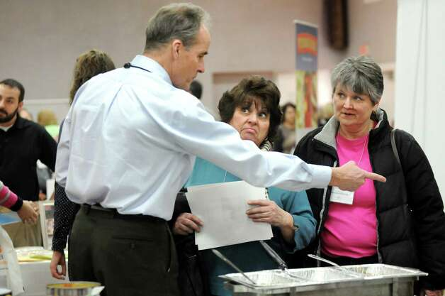 Joe Genther of Bush Brothers and Co., left, shares a recipe using black beans with cook managers Mary Lou Fanniff, center, and Elizabeth Ross, both with Shenendehowa School District, during a school food fair on Wednesday, Jan. 7, 2015, at the Polish Community Center in Colonie, N.Y. (Cindy Schultz / Times Union) Photo: Cindy Schultz / 00030089A