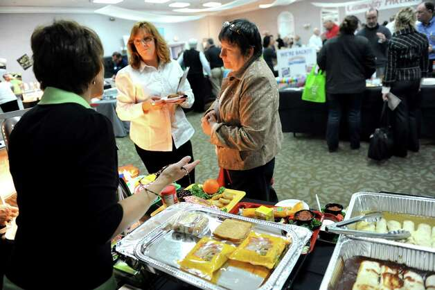 Food service managers Michelle Husek of Greater Johnstown Schools, center, and Melinda Madison of Northville and Wells School District, right, talk with Melissa DeCoffe of Advantage Waypoint during a school food fair on Wednesday, Jan. 7, 2015, at the Polish Community Center in Colonie, N.Y. (Cindy Schultz / Times Union) Photo: Cindy Schultz / 00030089A