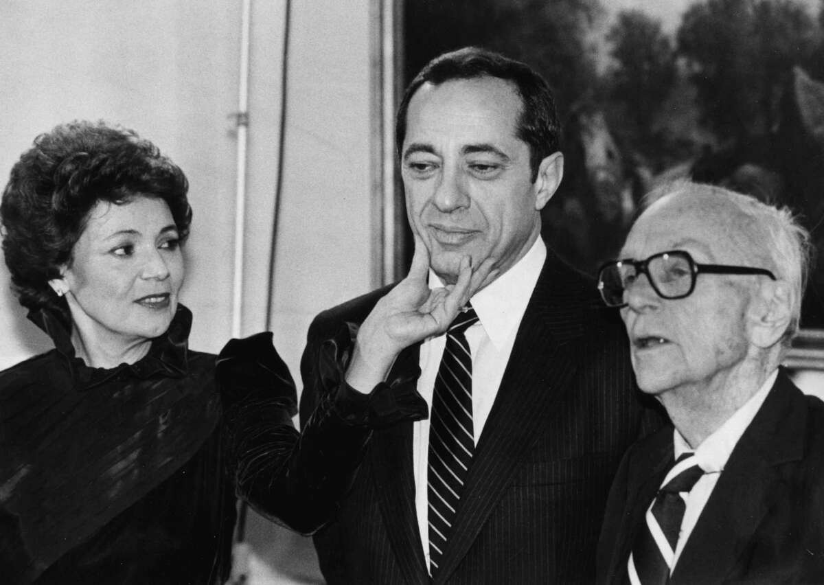 Matilda Cuomo squeezes the chin of her husband, Gov. Mario Cuomo, center, Jan. 3, 1983, during an event in Albany, N.Y. (Times Union archive)