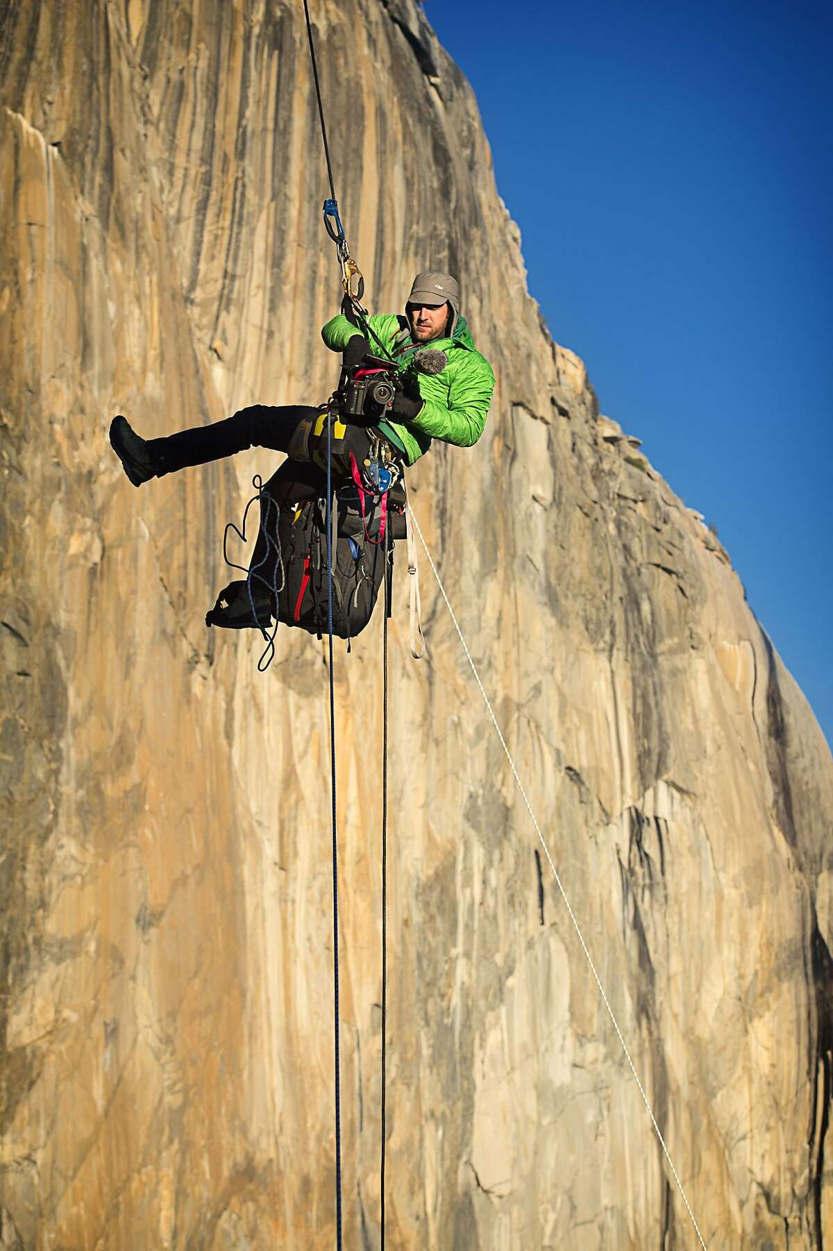 Tommy Caldwell hangs suspended in mid-air while using a video camera to document his and climbing partner Kevin Jorgenson's ascent of the Dawn Wall of El Capitan in Yosemite National Park, California, on Saturday, January 3, 2015.