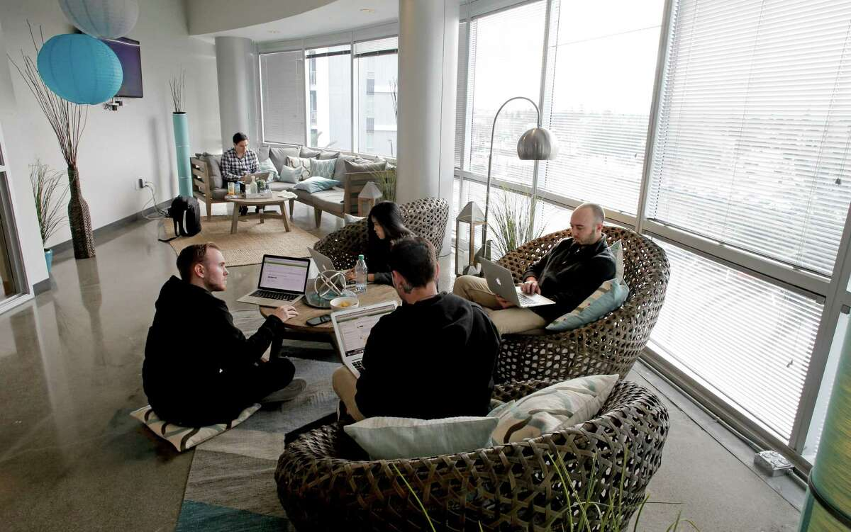 Employees work in the lobby area of the offices of Highfive in Redwood City.