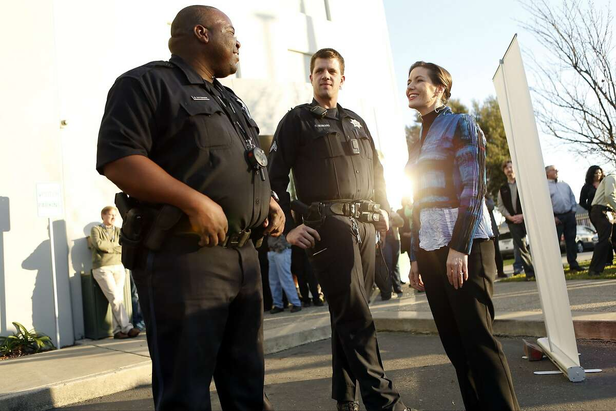 Oakland Mayor Libby Schaaf (right) visits with Oakland K-9 unit officers Marcel Patterson (left) and Robert Gerrans during visit to Pet Food Express corporate headquarters in Oakland, Calif. on Wednesday, January 7, 2015.