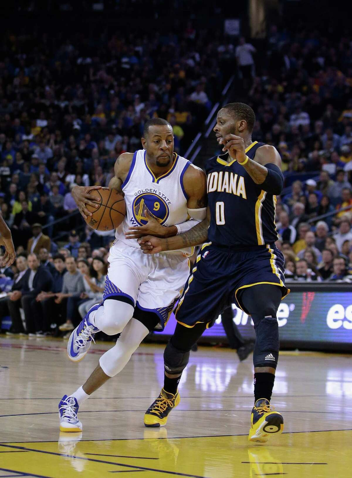 OAKLAND, CA - JANUARY 07: Andre Iguodala #9 of the Golden State Warriors drives on C.J. Miles #0 of the Indiana Pacers at ORACLE Arena on January 7, 2015 in Oakland, California. NOTE TO USER: User expressly acknowledges and agrees that, by downloading and or using this photograph, User is consenting to the terms and conditions of the Getty Images License Agreement. (Photo by Ezra Shaw/Getty Images)